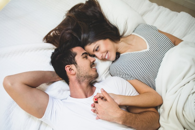couple-lying-on-the-bed-holding-hands-and-looking-into-each-other-s-eyes_23-2147596021