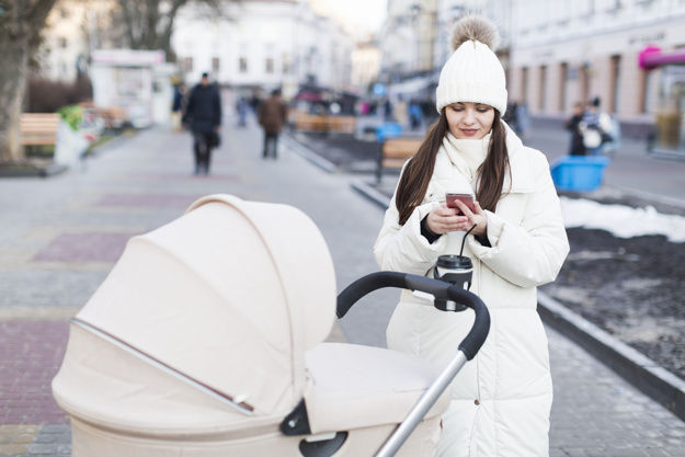 woman-with-baby-in-carriage-using-phone_23-2147778710.jpg