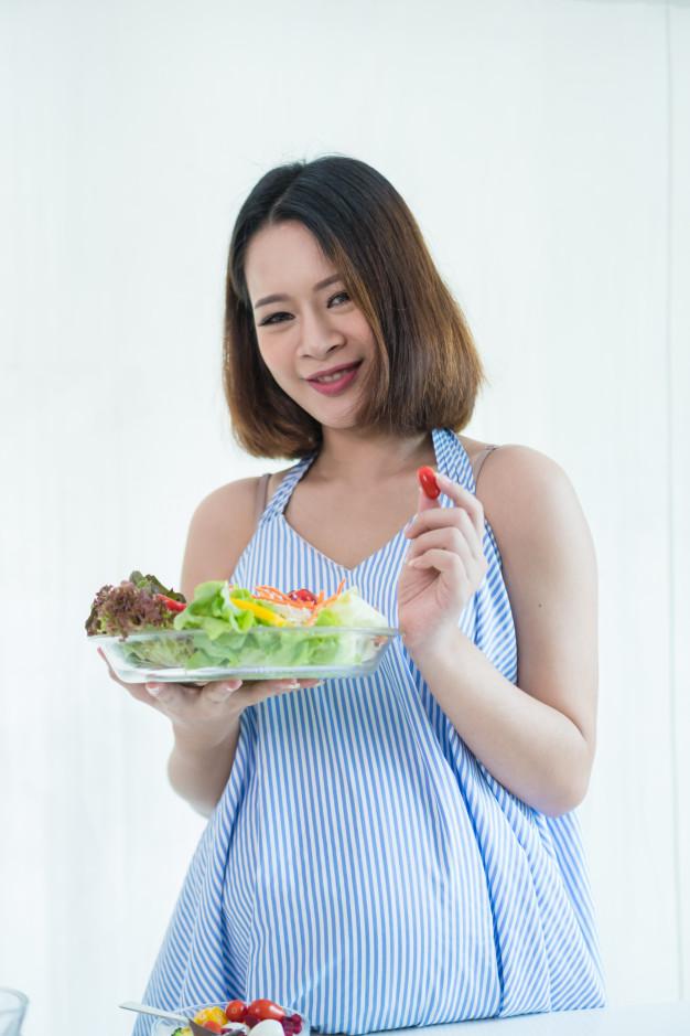 pregnant-women-put-on-a-blue-dress-she-eat-a-vegetable-salad-breakfastfor-healthy_40491-75