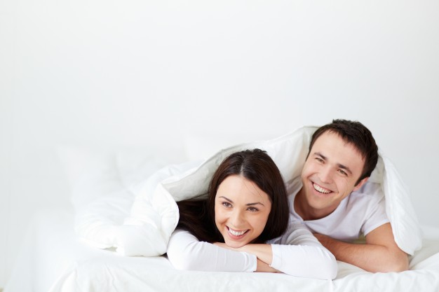 couple-laughing-in-bed_1098-3786
