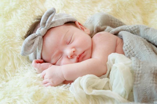 newborn-baby-girl-is-sleeping-on-fur-blanket_35666-347.jpg
